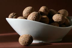 Walnuts. See portion of walnuts in white dish on brown background Royalty Free Stock Image