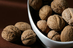 Walnuts. In a dish on brown background Royalty Free Stock Photo