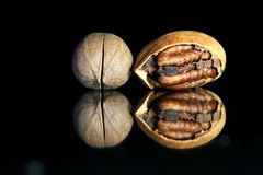 Walnuts. Two walnuts on the mirror with black background Royalty Free Stock Photos