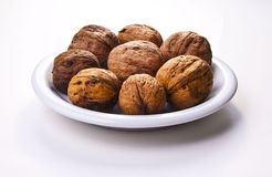 Walnuts. On white plate,  on a white background Royalty Free Stock Images