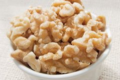 Walnuts. Shelled walnuts in a white bowl with a burlap background Royalty Free Stock Photography