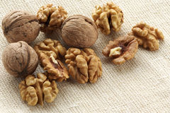 Walnuts. Whole and hulled walnuts on beige linen Stock Images
