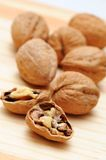 Walnuts. Cracked and whole walnuts on wooden table Stock Images