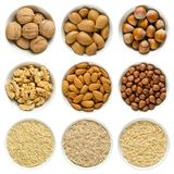 Walnuts, almond, hazelnuts in white bowls on white background stock image