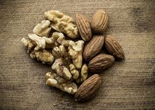 Walnuts and almonds from above. A mix of walnuts and almonds on a wooden board. The image can be used for multiple subjects, such as: food, organic, health, home Royalty Free Stock Photo