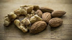 Walnuts and almonds clear. A mix of walnuts and almonds on a wooden board. The image can be used for multiple subjects, such as: food, organic, health, home and Stock Photos