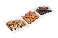 Walnuts almonds and dates in a white dish Royalty Free Stock Photos