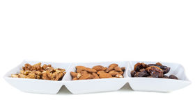 Walnuts almonds and dates in a white dish Stock Image