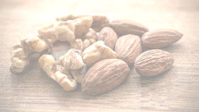 Walnuts and almonds. A mix of walnuts and almonds on a wooden board. The image can be used for multiple subjects, such as: food, organic, health, home and Stock Photography