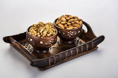 Walnuts and almonds in a wooden bowl and tray. Very good for health stock photography
