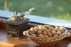 Walnuts and Antique Coffee Grinder. Bowl of walnuts in the shell on a window ledge next to an antique coffee grinder royalty free stock photos