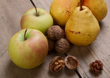 Walnuts, apples and pears. On the old wooden table Stock Images