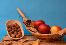 Walnuts and apples on wooden bamboo bowls Royalty Free Stock Images