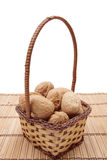 Walnuts in basket. Basket of brown walnuts on white background Royalty Free Stock Photo
