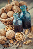 Walnuts in basket and nuts tincture or oil on old table Royalty Free Stock Image