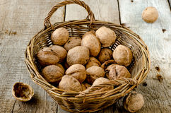 Walnuts in the basket. On a wooden board Stock Photo