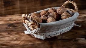 Walnuts in a basket on wooden table royalty free stock photo