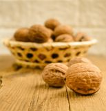 Walnuts in basket on wooden table stock image