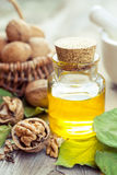 Walnuts, bottle of essential oil and basket with nuts on old kit Stock Images