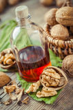 Walnuts, bottle of tincture or oil and wicker basket with nuts o Stock Photo