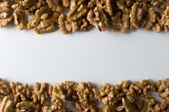 Walnuts at the bottom and top of a white table. Top view. Background with copy space. Nuts.  stock images