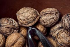 Walnuts in a brown earthenware bowl with a metallic nut cracker royalty free stock image