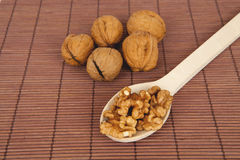 Walnuts on a brown wooden background with wooden spoon Stock Image