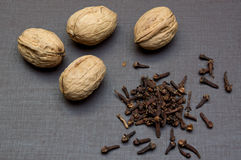 Walnuts and buds of the clove tree closeup on black table. Royalty Free Stock Photo