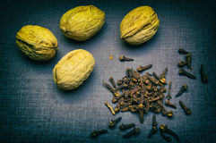 Walnuts and buds of the clove tree closeup on black table. Stock Image