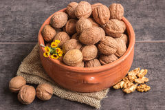 Walnuts in a ceramic bowl and a small bouquet of wild flowers Stock Image