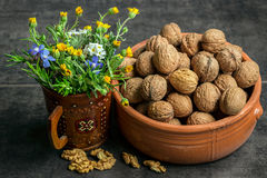 Walnuts in a ceramic pot  with a bouquet of wildflowers Stock Images