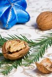 Walnuts, Christmas ornaments and fir. Cracked walnut on fir branch on holiday napkin with Christmas blue star royalty free stock photos