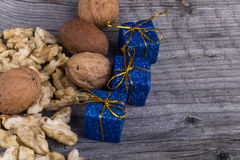 Walnuts and Christmas package on a wooden background. Walnuts and blue christmas package on a wooden background Stock Photography