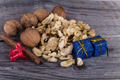 Walnuts, cinnamon and Christmas package on a wooden background. Walnuts, cinnamon with red bow and blue christmas package on a wooden background Royalty Free Stock Photography