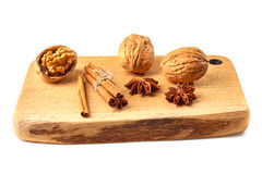 Walnuts, cinnamon sticks and star anises on wooden board. Stock Images