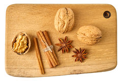 Walnuts, cinnamon sticks and star anises on wooden board. Royalty Free Stock Image