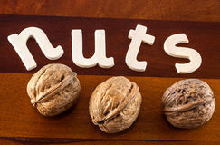 Walnuts. A close up  of  the word nuts with walnuts  on a wooden board Stock Image