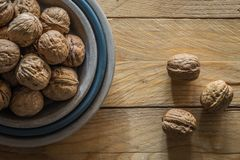 Walnuts closeup inside plate over wooden board royalty free stock photography