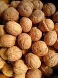 Walnuts. Closeup to lots of Walnut kernels and whole walnuts .Full background Stock Photos