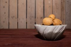 Walnuts in a concrete cup and place for text. wooden background. horizontal view royalty free stock photography