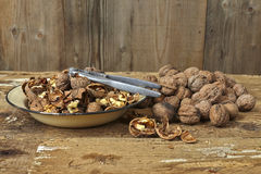 Walnuts cracked open with old nut cracker in a vintage plate on Royalty Free Stock Images