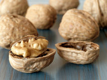 Walnuts. Cracked and whole walnuts on wooden blue table Stock Photo