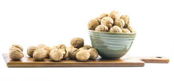 Walnuts in a cup on a wooden board and on a white background Royalty Free Stock Image