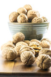 Walnuts in a cup on a wooden board and on a white background - front view Stock Image