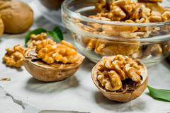 Walnuts in a glass bowl. On a rustic background royalty free stock image