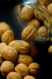 Walnuts in glass jar. A glass jar with whole walnuts spilling out stock photography