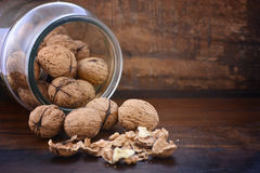 Walnuts in glass jar on wood table. Stock Photography