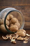 Walnuts in glass jar on wood table. Stock Photo