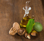 Walnuts in green husk with leaf and oil Stock Photo