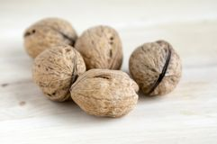 Walnuts in hard shells, pile on wooden background, fruits in hard shells royalty free stock photo